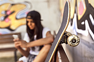 Skateboard and young woman with cell phone in background - MGOF02766