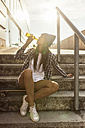 Young woman sitting on skateboard drinking a beer from the bottle - MGOF02778