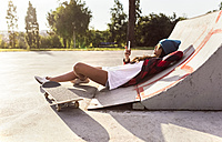 Young woman with skateboard and cell phone in a skatepark - MGOF02781