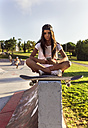 Young woman with skateboard and cell phone in a skatepark - MGOF02784