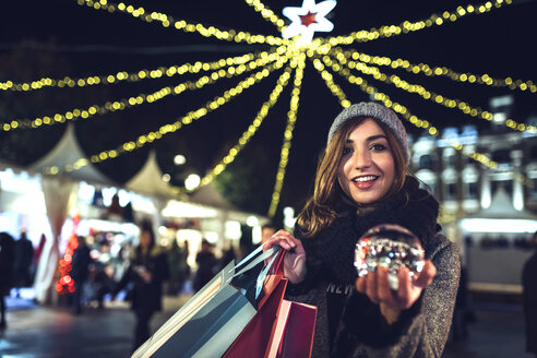 Portrait of happy woman holding bags and snow globe on the Christmas Market - DAPF00529