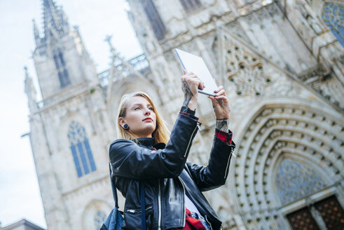 Spain, Barcelona, young woman taking picture with tablet in front of cathedral - KIJF01038