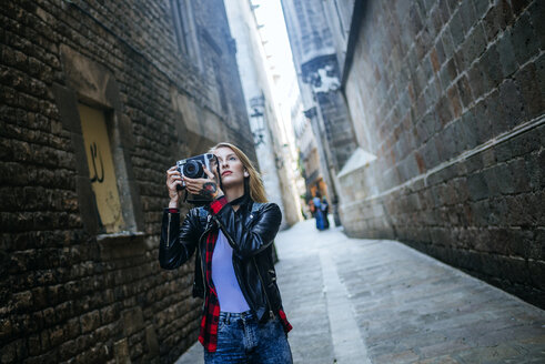 Spain, Barcelona, young woman taking pictures with reflex camera at Gothic Quarter - KIJF01041