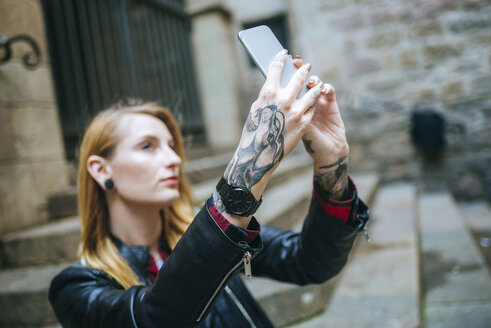 Tattooed woman's hands taking selfie with cell phone - KIJF01044