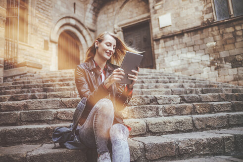 Spain, Barcelona, smiling young woman sitting on stairs looking at tablet - KIJF01050