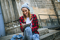 Spain, Barcelona, smiling young woman sitting on stairs writing in notebook - KIJF01053