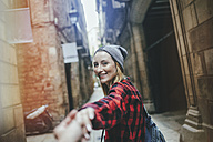 Spain, Barcelona, portrait of smiling young woman holding hands at Gothic Quarter - KIJF01062