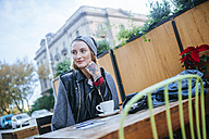 Young tattooed woman sitting in pavement cafe - KIJF01074