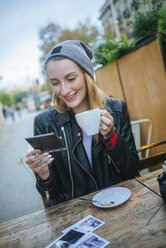 Young tattooed woman sitting in a pavement cafe looking at photos - KIJF01077