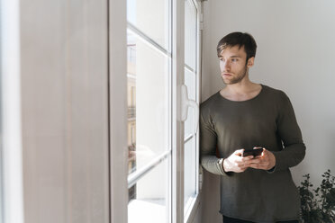 Young man with smartphone looking through window - KKAF00291