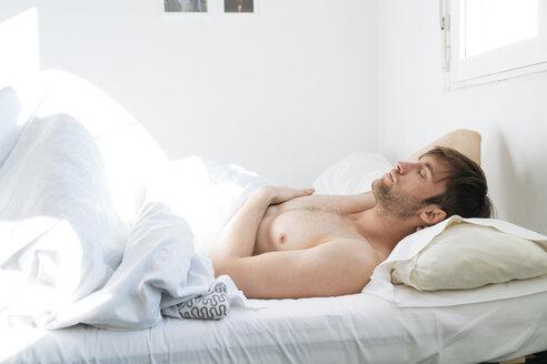 Man relaxing in bed - KKAF00294