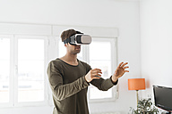 Young man wearing virtual reality glasses at home - KKAF00300
