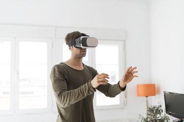 Young man wearing virtual reality glasses at home - KKAF00300