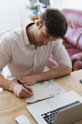 Young man with city map and laptop  at home - KKAF00306