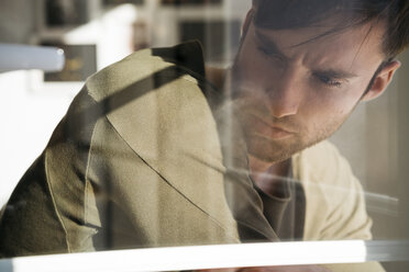 Young man lost in thought behiing windowpane - KKAF00312