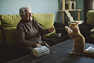 Senior woman playing with her kitten at home - RAEF01635