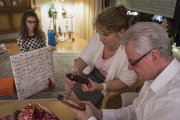 Gift giving at Christmas eve, grandparents looking at bottles - PAF01740