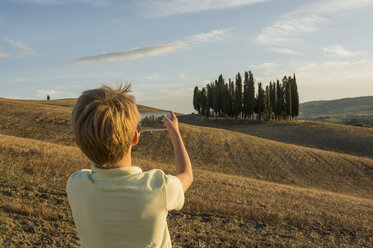 Italy, Tuscany, Boy taking pictures of landscape - PAF01749