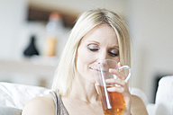 Blond woman enjoying glass of tea - CHPF00363