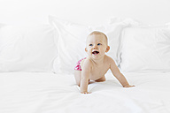 Happy baby playing around girl on white bed - LITF00486