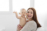 Mother holding waving little baby girl - LITF00492