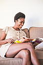 Young woman sitting on the couch reading magazine - SIPF01291