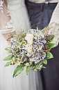 Close-up of bride and groom holding bridal bouquet - ASCF00691