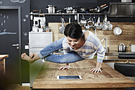 Woman doing a handstand on table in kitchen looking on tablet - FMKF03459