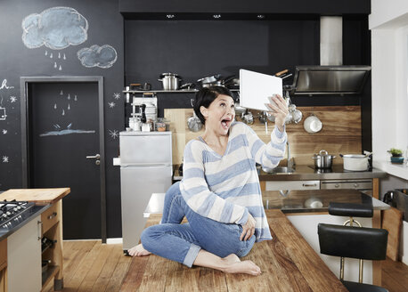Woman sitting on table in kitchen taking a selfie with tablet - FMKF03462