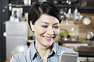 Smiling woman in kitchen looking at cell phone - FMKF03465
