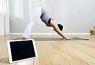Woman practising yoga behind tablet - FMKF03468