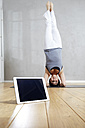 Woman practising yoga doing a headstand behind tablet - FMKF03471