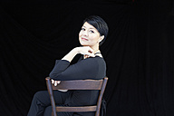 Portrait of smiling woman sitting on chair - FMKF03480