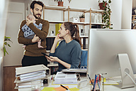 Smiling mother at desk looking at father holding baby in home office - MFF03425
