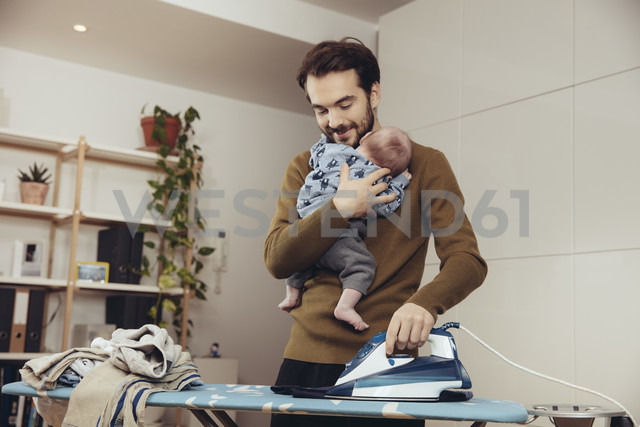 Father ironing and holding his baby at home - MFF03437