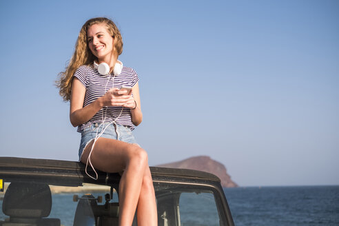 Young woman sitting on car on the beach - SIPF01310