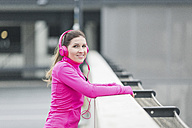 Portait of smiling sportive woman wearing headphones - ASCF00709