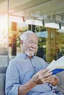 Senior man sitting on terrace reading book - RORF00439