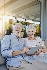 Senior couple sitting on terrace using digital tablet - RORF00442
