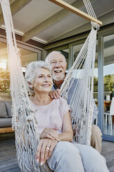 Senior couple on terrace, woman sitting in hammock - RORF00448