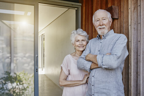 Senior couple standing in front of their house, looking confident - RORF00451
