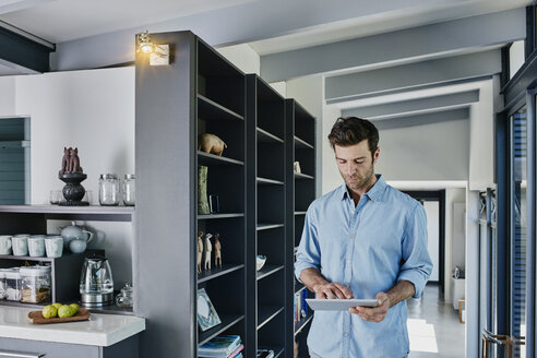 Man regulating light with his digital tablet - RORF00454