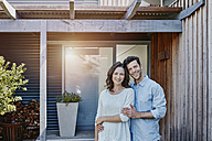 Couple standing in front of door of their home - RORF00472