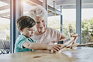 Grandson and grandmother playing with toy airplane - RORF00475