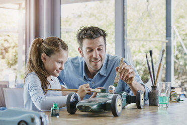 Father and daughter painting a toy race car - RORF00478