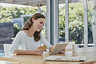 Woman sitting on terrace, doing online payment with credit card - RORF00517
