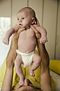 Newborn baby in diapers being held up by father - MFF03457