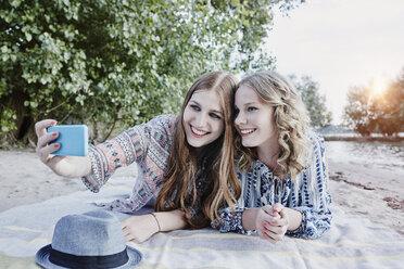 Two teenage girls lying on blanket on the beach taking selfie - RORF00524
