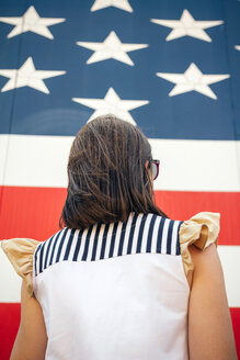 USA, back view of woman in front of Stars And Stripes - DAPF00542