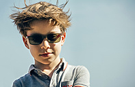 Portrait of cool boy with sunglasses and blowing hair in front of sky - DAPF00551